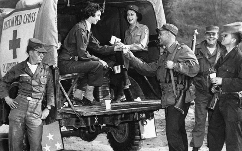 A black and white photo of WWII soldiers receiving coffee from two women
