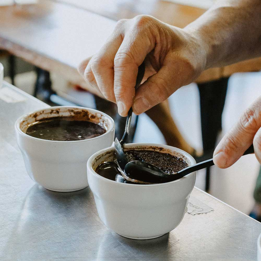 A barista performing coffee cupping.