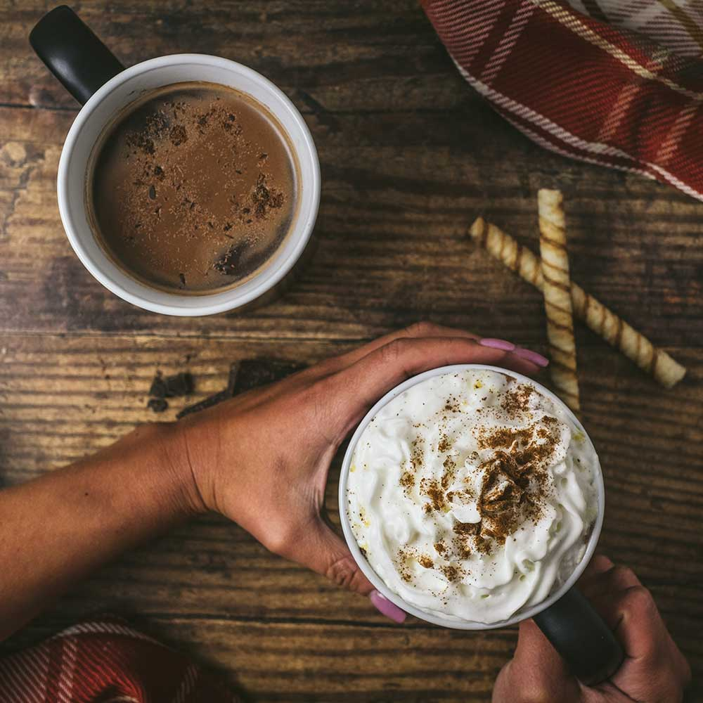 Two mugs of coffee on a table with whip cream and foam on top.