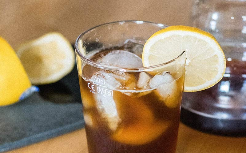 A clear glass filled with coffee soda and ice cubes with a lemon garnish.