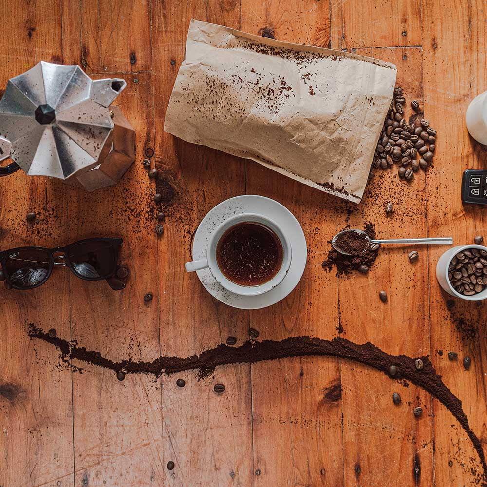 A mug of coffee, a coffee pot, a bag of coffee beans, sunglasses and coffee grounds laid out on a wooden table.