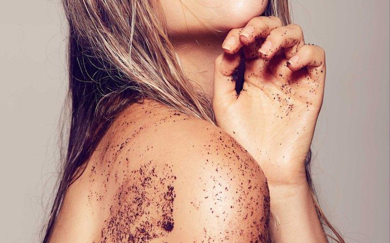 An image of coffee grounds on a woman's shoulder in the shower.