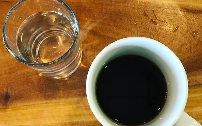 Cup of coffee next to a glass of water