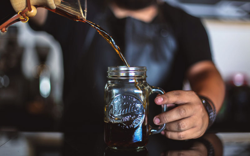 A male barista is shown pouring cold brew coffee from a Chemex coffee maker into a Mason jar