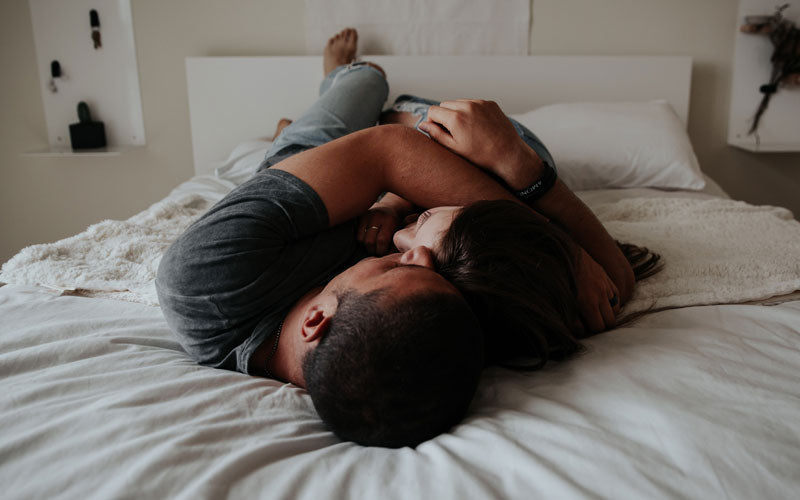 "Two people lay on a bed and cuddle as part of what's called ""cuddle therapy"""