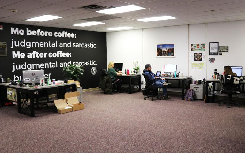 A photo of the Death Wish Coffee office in 2019. There are three people sitting at desks and a black wall.