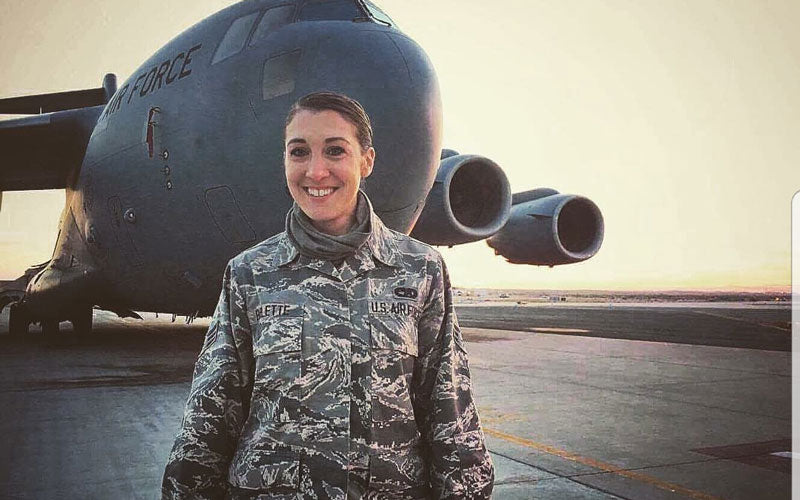 A photo of Danielle LaGuardia-Barlette in an Air Force uniform in front of a plane. She's active duty in the military and part of the Death Wish team.