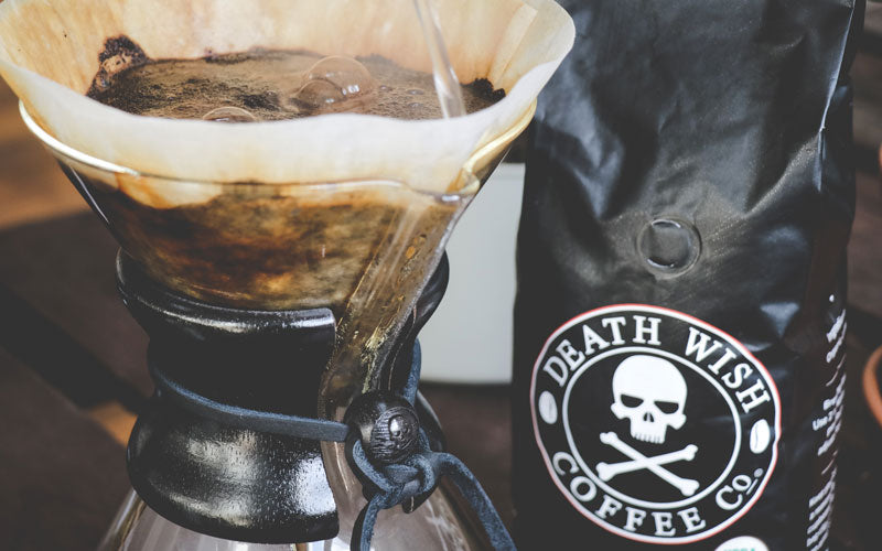 A Chemex coffee machine shown being brewed next to a black bag of Death Wish Coffee