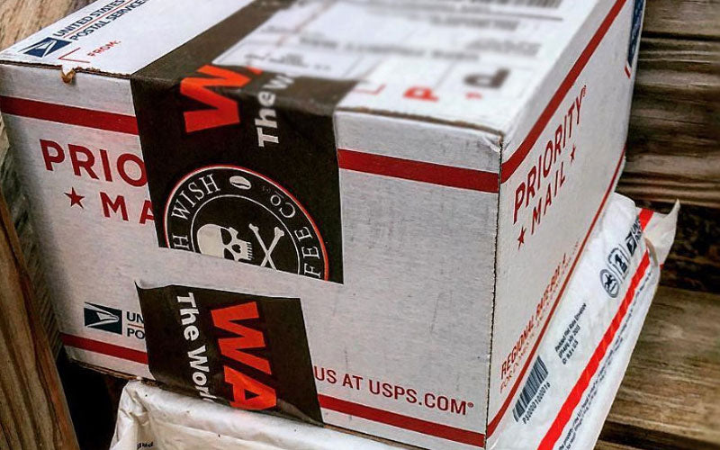 A white USPS package with black and red Death Wish packaging tape sitting outside of a house