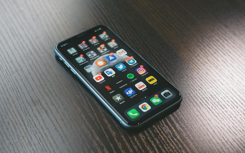 An iPhone sitting on a table displaying apps like Netflix, Twitter, and Instagram
