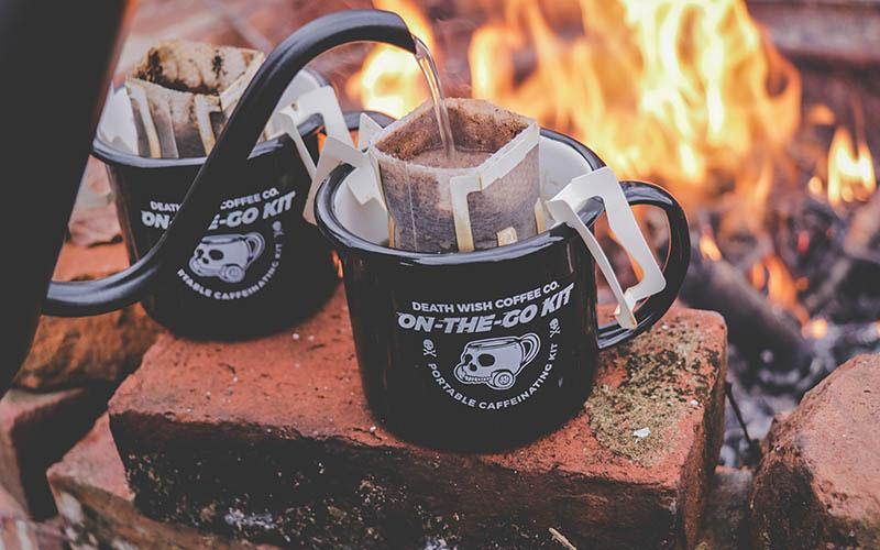 Two black mugs of single-serve pour-over coffee being made by a campfire
