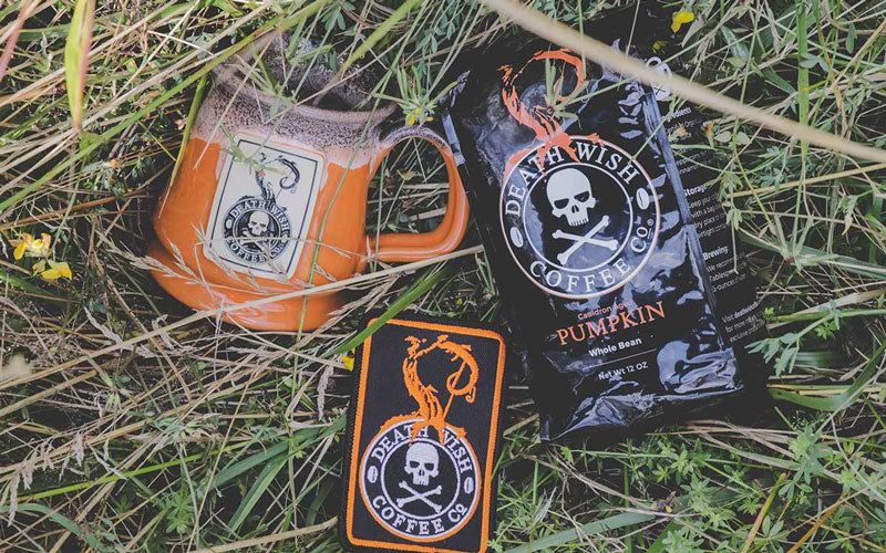 An orange coffee mug with a Death Wish Pumpkin logo sits next to a matching patch and a bag of Death Wish Pumpkin Coffee