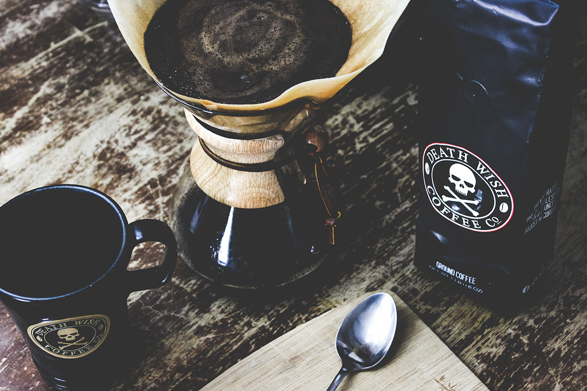 A Chemex coffee maker on a table next to a bag of Death Wish Coffee and a black coffee mug