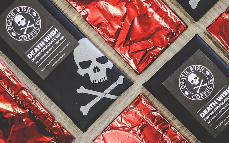 A picture of Death Wish chocolate bars sitting on a table. Some are wrapped in red foil, and others show our skull and crossbones logo on the wrapper.