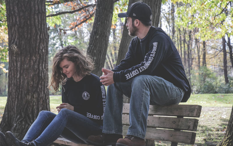 Man and woman sitting, donned in Death Wish Coffee long-sleeve shirts