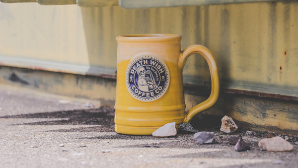 Death Wish Coffee's mug depicting Rosie the Riveter. It's a yellow mug with a blue mug medallion