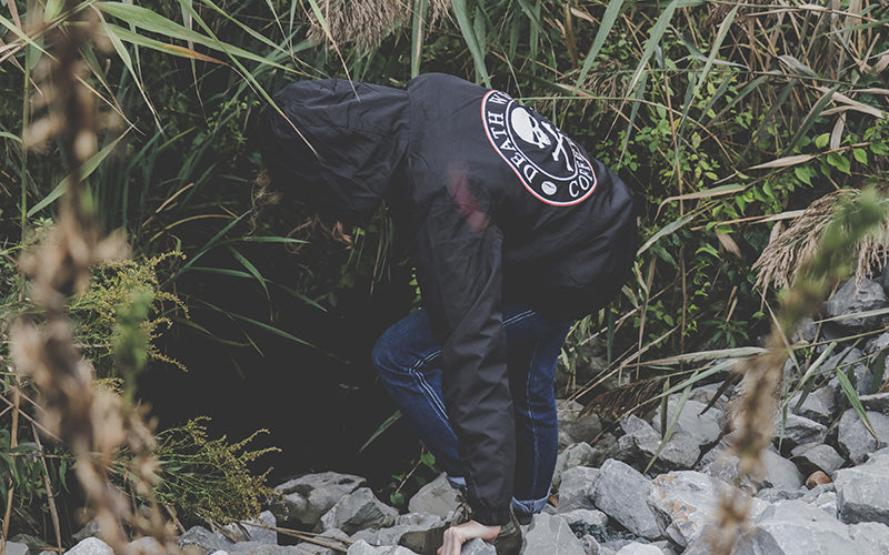 Person traversing rocks while wearing a Death Wish Coffee windbreaker