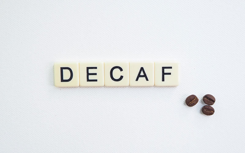 "Whites tiles on a table that spell out the word ""Decaf"""