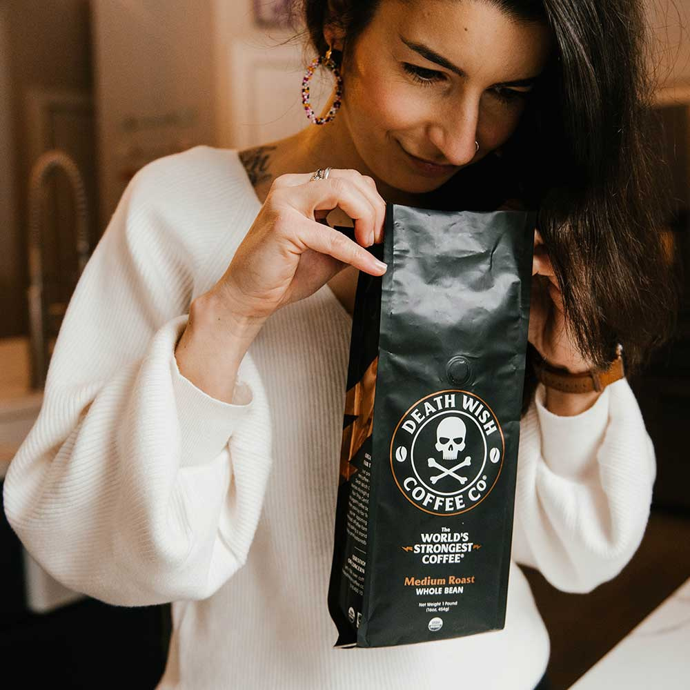 A female smelling a bag of the World's Strongest Medium Roast coffee.