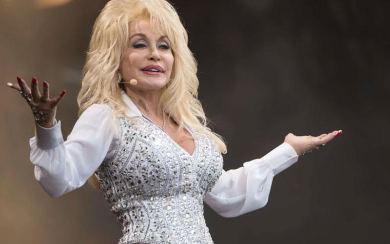 A photo of country singer Dolly Parton on stage singing in a white jumpsuit