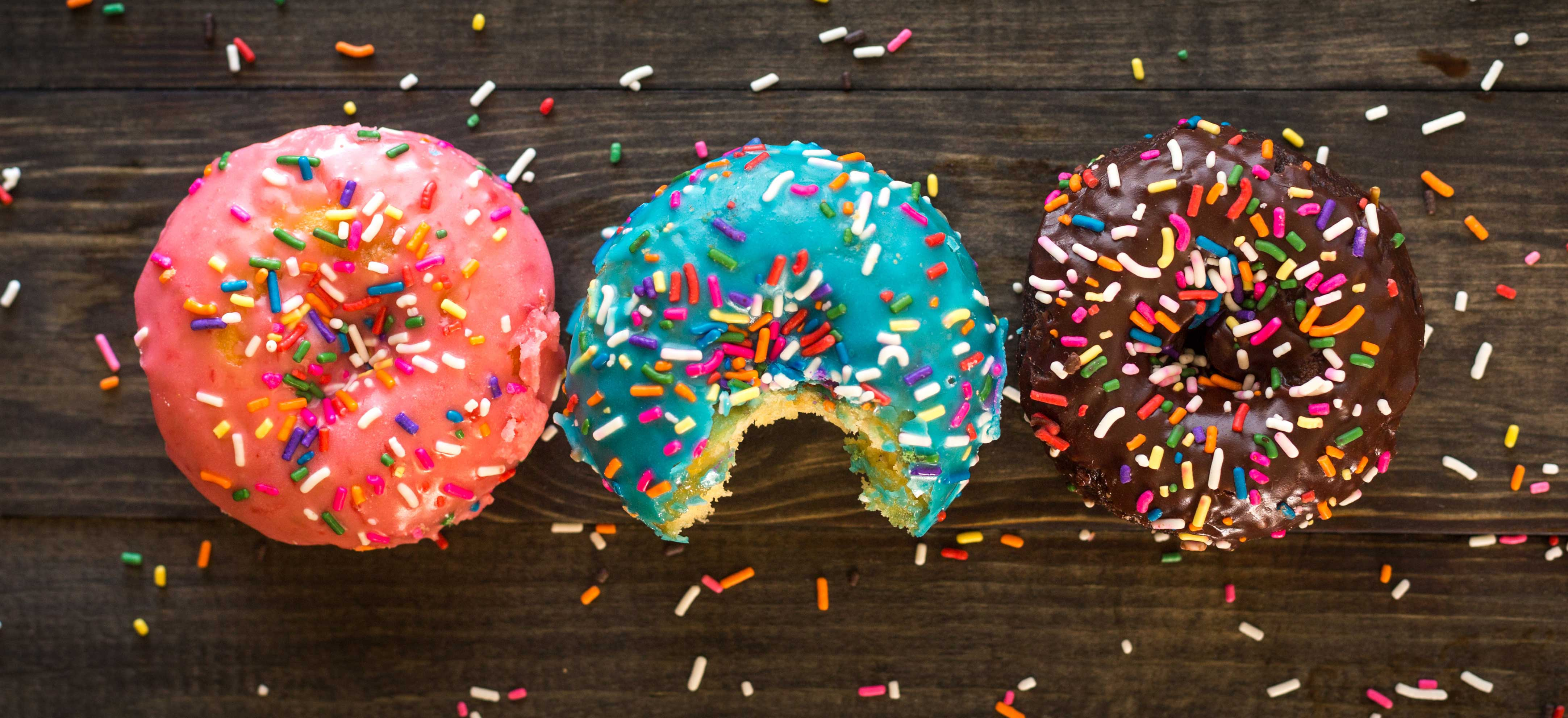 An image of 3 frosted donuts on a table.