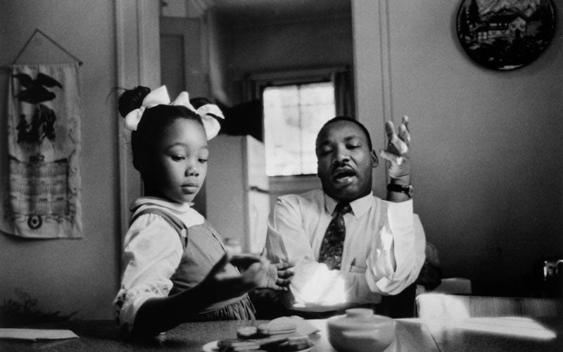 A photo of Dr. Martin Luther King Jr. sitting at a kitchen table with his daughter