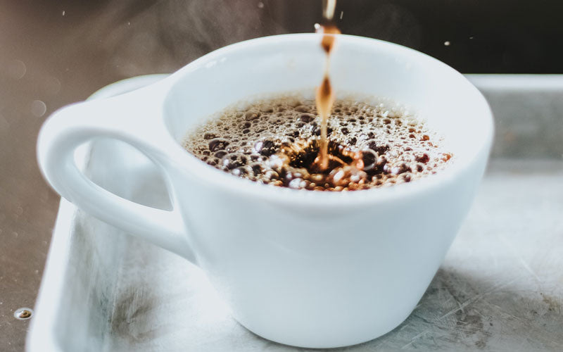 A white ceramic coffee mug being filled with hot coffee. A new study found that drinking coffee can help prevent gallstones.