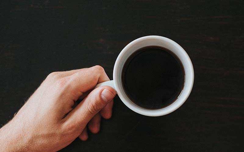 A hand holding a white mug full of black coffee on a black countertop.
