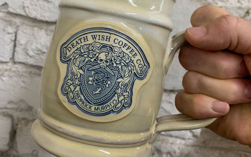 A tan Dropkick Murphys coffee mug