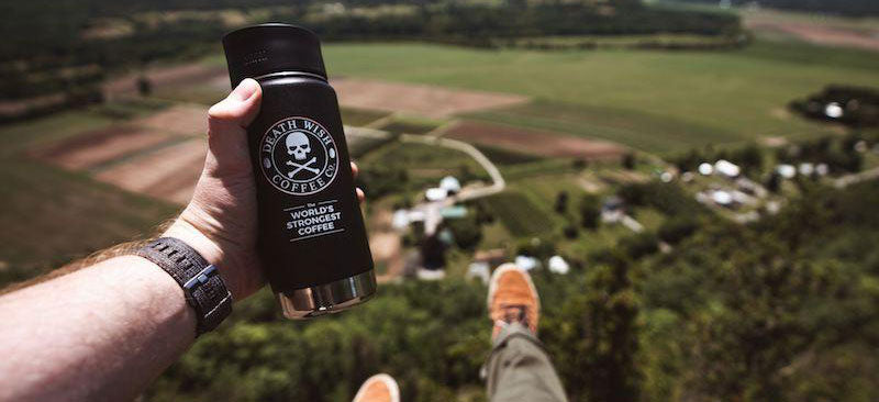 Man overlooking a vista, feet outstretched, holding a Death Wish travel mug