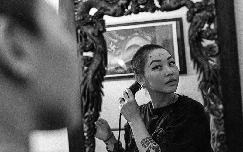 A photo of artist Emily Leung doing shaving her head in the mirror