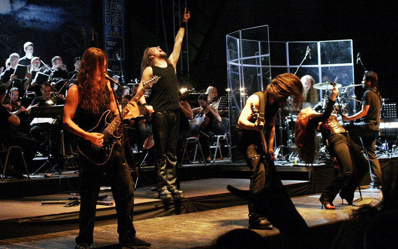 Epica, a Dutch symphonic metal band, performs on stage with a symphony behind them