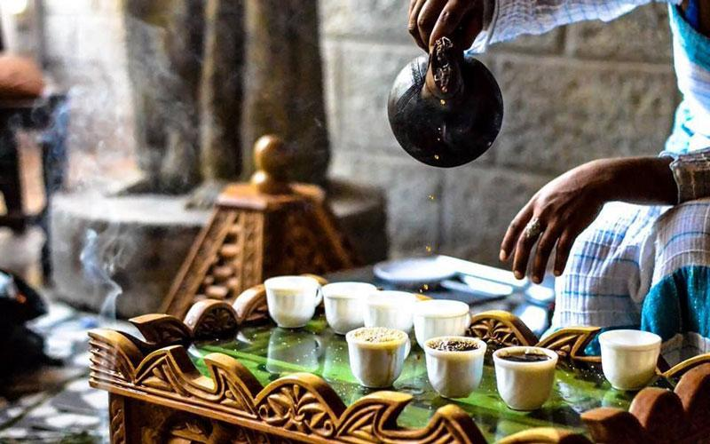 Coffee being poured into small glasses during an Ethiopian Coffee Ceremony