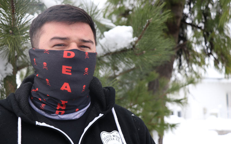 A male shown wearing a black and read bandana as a face mask in the snow
