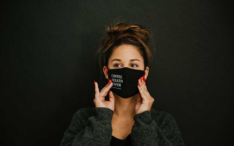 """Woman wearing a Death Wish face mask that reads: """"Coffee Breath Cover"""""""