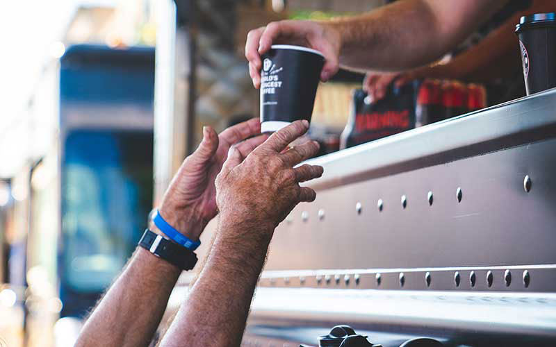 A person's hands reaching up to receive a to-go cup of Death Wish Coffee