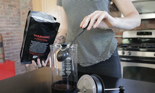 Woman adding coffee to a french press