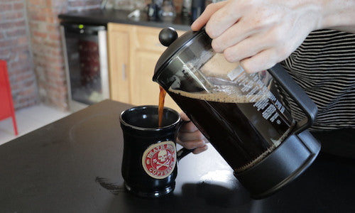 Woman pouring coffee from a french press into a mug