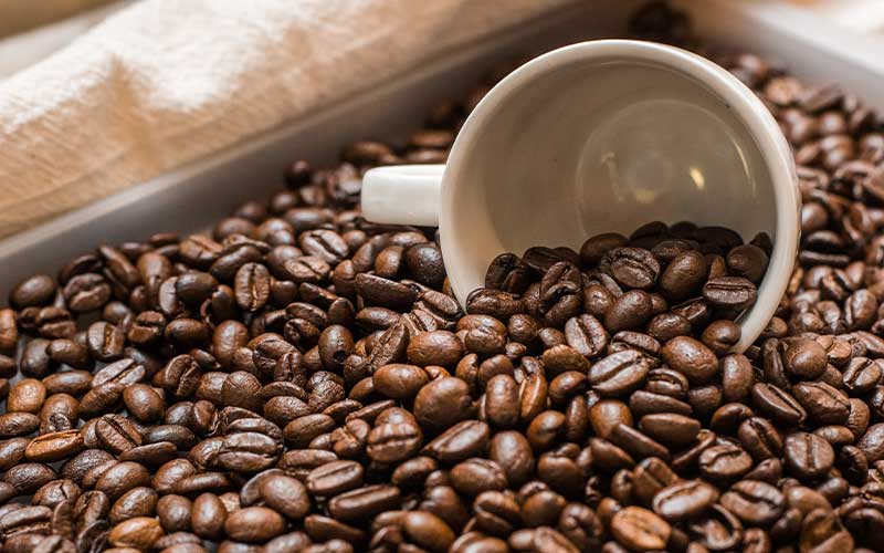 An image of coffee beans pouring out of a mug.
