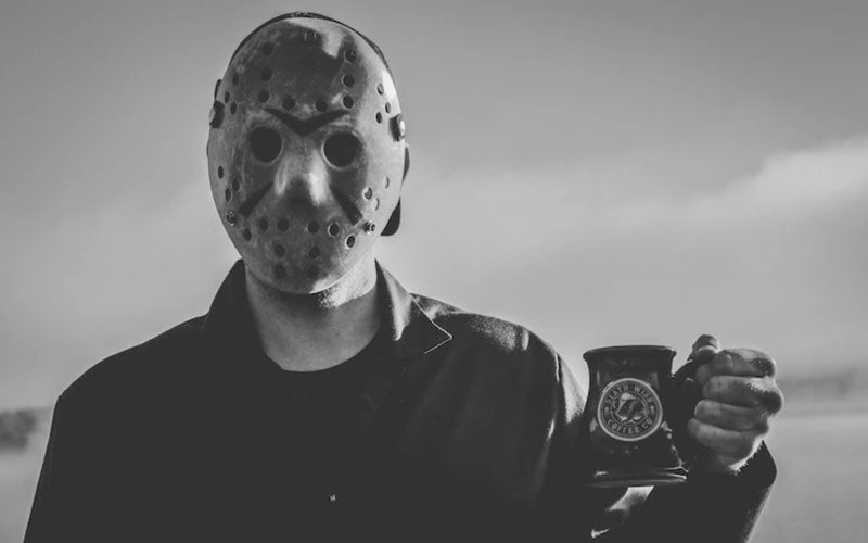 "A black and white photo of a Death Wish employee wearing a ""Friday the 13th"" mask and costume while holding a Friday the 13th coffee mug"