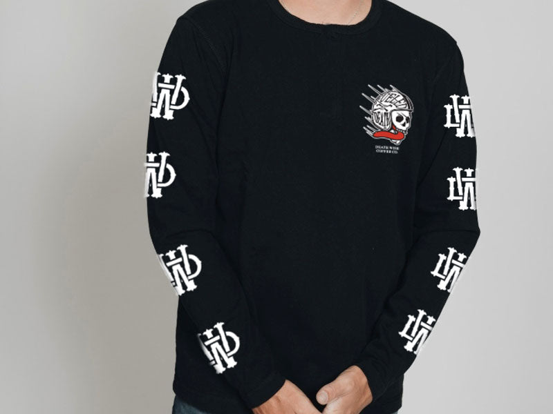 "A product shot of a long-sleeve black T-shirt that includes ""DW"" logos on the sleeves and a logo on the front that depicts a skull wearing a helmet on the front that says ""Fueled by Death"""