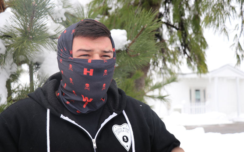 A male wearing a black and red bandana that covers his entire face except for his eyes