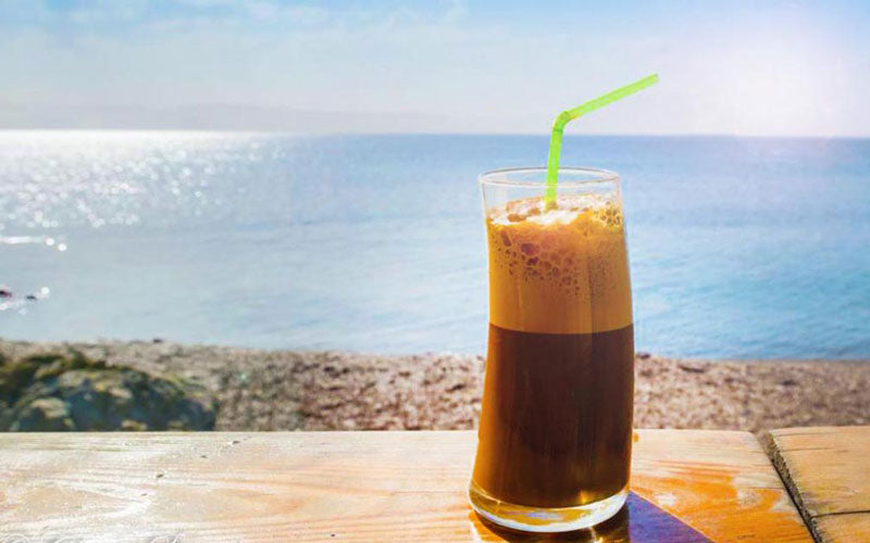 A Greek Frappe sits in a glass with a view of the ocean in the background
