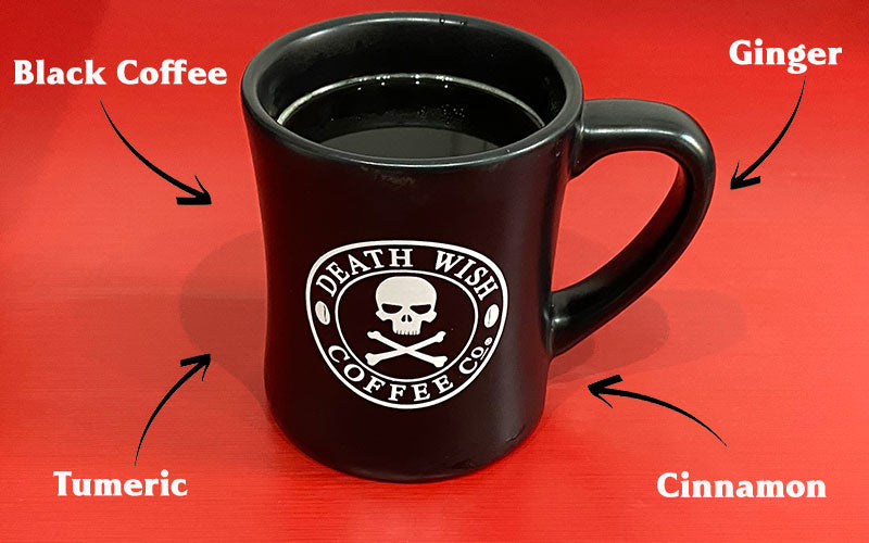 A black coffee mug with the white Death Wish Coffee Co. logo in the center. The background is orange and has ingredients written out with arrows pointing to the mug. The ingredients are coffee, ginger, turmeric, and cinnamon.