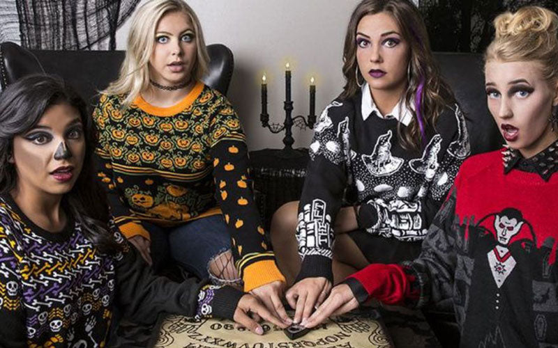 A group of girls sit around a Ouija board wearing Halloween sweaters