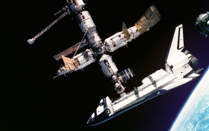 A photo from NASA of a Space Shuttle attaching to a Space Station above Earth