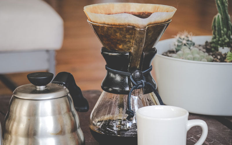 A Chemex coffee machine pictured brewing coffee next to a white coffee cup and tea kettle