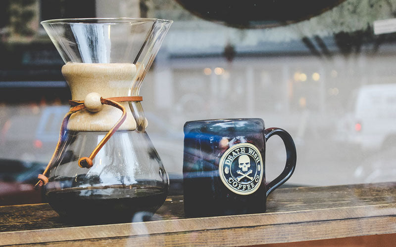 A photo of a Chemex coffee maker filled with coffee next to a mug shown on the counter in the window of a cafe