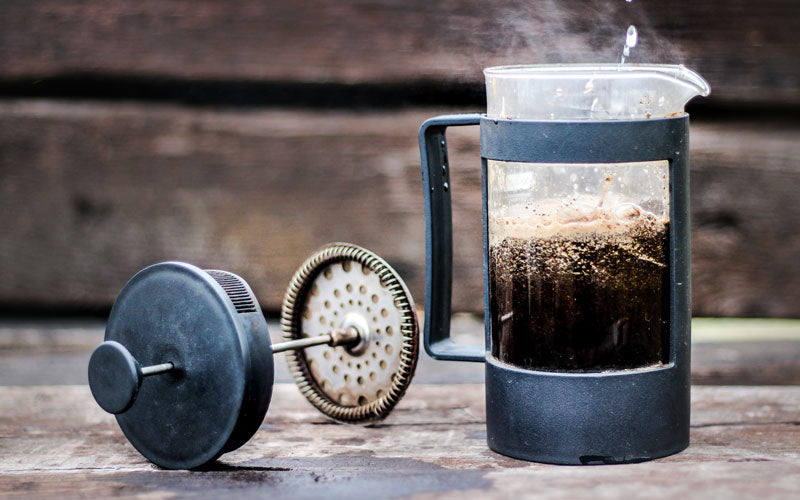 A photo of a French Press coffee maker filled with coffee on a wooden table