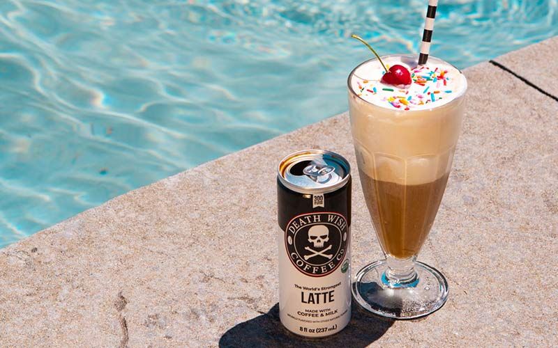 A ice cream float sitting next to a canned latte next to a pool.